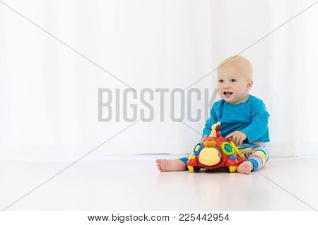 Adorable Baby Boy Learning To Crawl And Playing With Colorful Motion Toy In White Sunny Bedroom. Cut