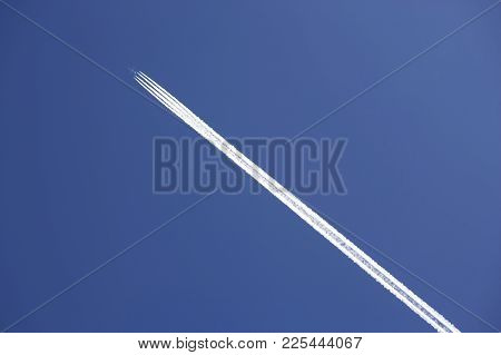 Four Engine Jet Airliner With Exhaust Vapour Trails In Clear Blue Sky
