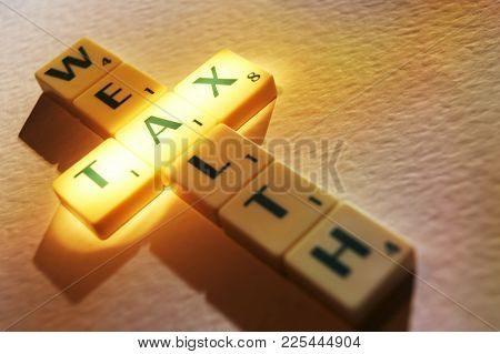 Cleckheaton, West Yorkshire, Uk: Scrabble Board Game Letters Spelling The Words Tax Wealth, 1st June
