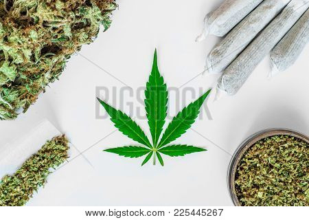 Leaf Of Cannabis, Buds Of Marijuana, Joint Unrolled Weed And A Grinder With Crushed Weed On A White