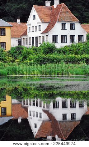 An Almost Perfect Reflection Of A House, Bushes, Shoreline Reeds And Flowers In A Pond.  There Are M