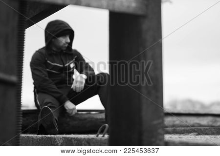 Handsome Sportsman Is Resting On A Gateway Block During A Brake In Outdoor Running Workout. Face Is