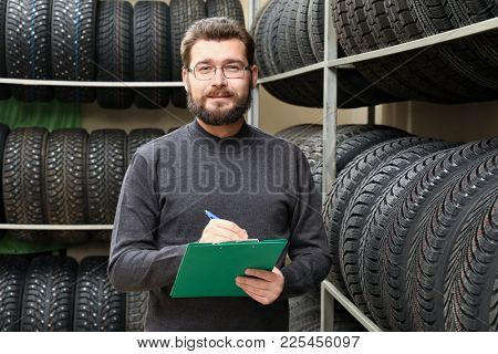 Salesman with clipboard near tires on racks in automobile store