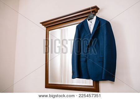 Blue Wedding Suit On Hangers For Groom At Room.