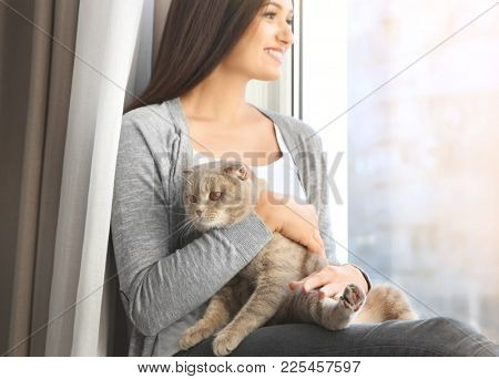 Young woman with cute pet cat sitting on windowsill at home