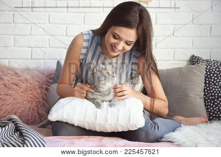 Young woman with cute pet cat on sofa at home