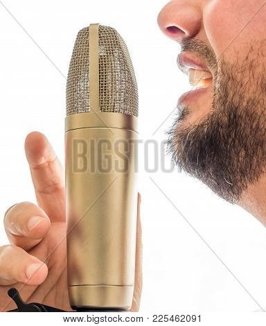 An Old Fashioned Gold Microphone Is Set Infront Of A Males Face. The Male Is Singing Into The Microp