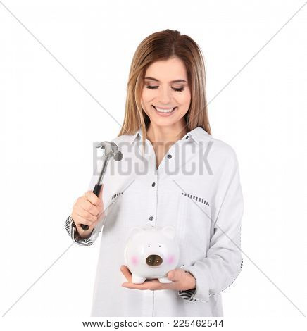 Young woman holding hammer over piggy bank on white background