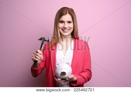 Young woman holding hammer over piggy bank on color background