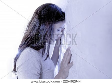 Expressive Portrait Of Young Sad And Depressed Hispanic Woman With Head Against The Wall Looking Des