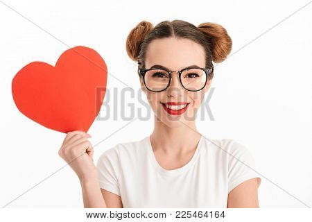 Close up portrait of a happy casual girl in eyeglasses holding paper heart and looking at camera isolated over white background