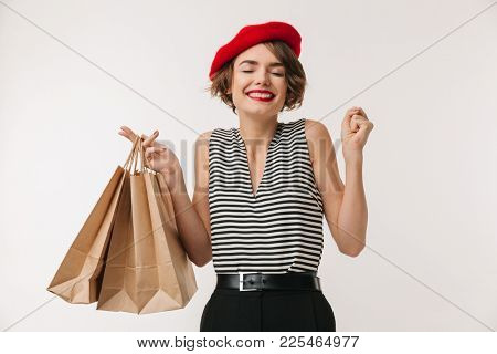 Portrait of elegant woman in striped shirt and red beret smiling while carrying shopping bags isolated over white background