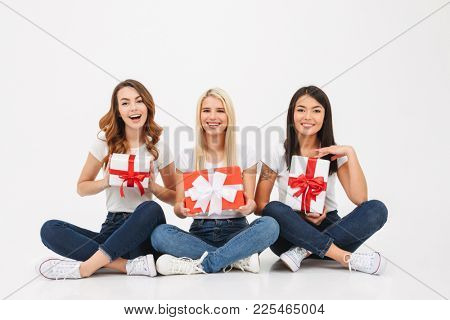 Photo of three young cute pretty girls friends sitting isolated over white background looking camera holding surprise gifts boxes.