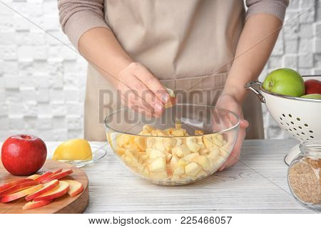 Woman putting cut apples in glass bowl on kitchen table