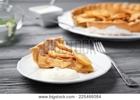 Plate with piece of tasty apple tart on wooden table
