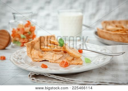 Plate with piece of tasty apple tart on table