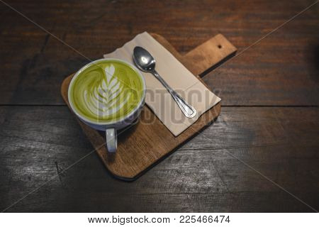 Hot Matcha Latte In White Cup With Small Spoon And Napkin On Wood Table, Tea Break In Thailand