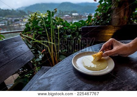 Fried Steamed Bun Was Dip In The Sweetened Condensed Milk In A Bowl With Mountain Village Background