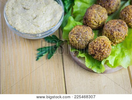 Bowl With Tahina Sauce And Falafels On A Salad Sheet On A Wooden Table. Eastern Vegetarian Meal Of C