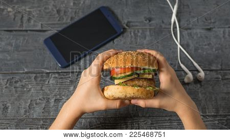 The Girl Holds A Freshly Prepared Burger Over A Table With A Phone And Headphones. Freshly Prepared