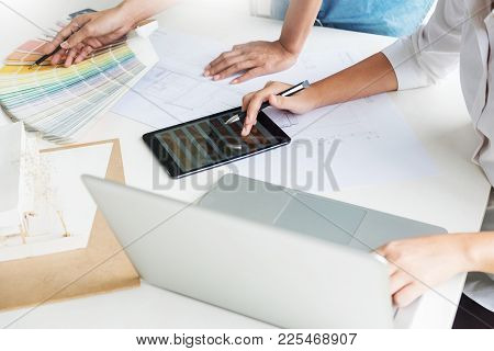 Creative Or Interior Designers Teamwork With Pantone Swatch And Building Plans On Office Desk, Archi