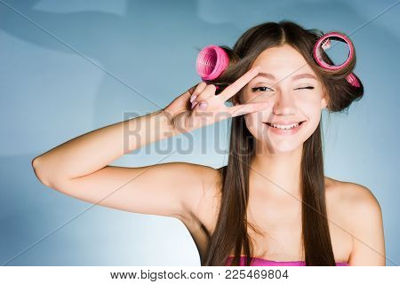 Happy Smiling Girl Showing Two Fingers On Head Of Curler
