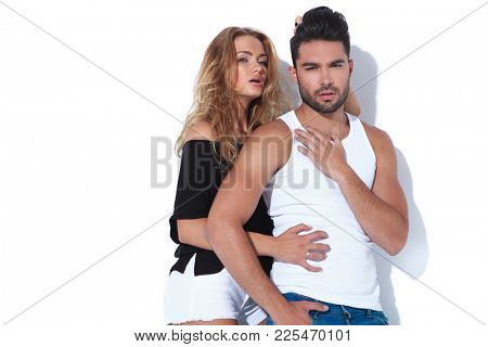 sexy woman pulling her boyfriend's hair and embraces him on white background