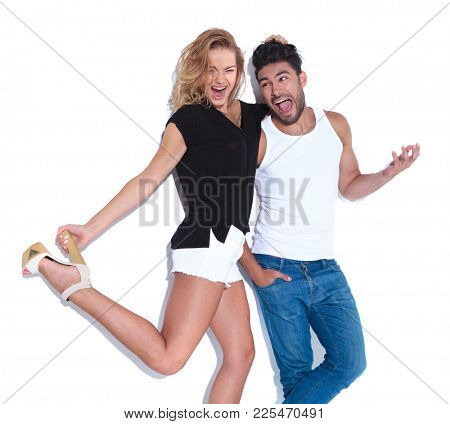 crazy couple having fun together, woma is pulling his hair on white background