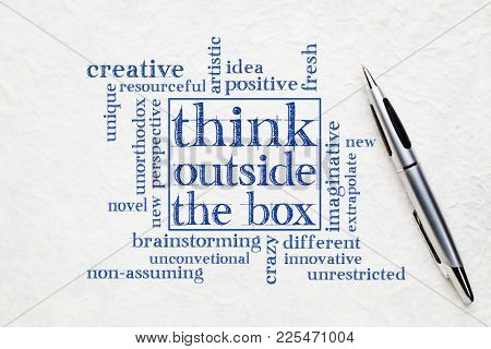 Think outside the box concept - word cloud on a textured white paper with a pen