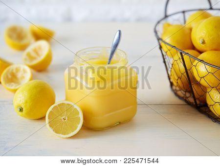Jar of homemade lemon curd. Lemon curd in a glass jar with sliced lemons.
