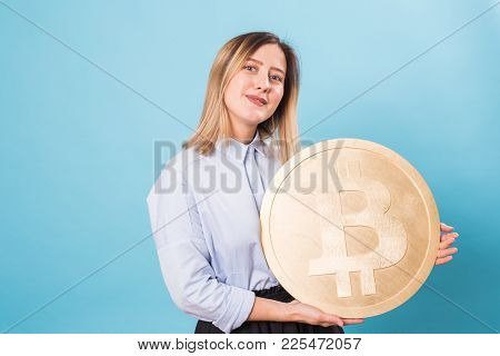 Cryptocurrency And Economy Concept - Young Woman Holds A Gold Bitcoin.