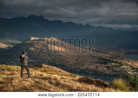 Young Male Photographer Taking Photo In Photographing Posture With Mountain Scenery During Golden Ho