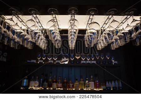 Empty Wine Glasses Hanging Upsidedown In Bar Interior. Classic Wineglasses Hanger On Restaurant Or P