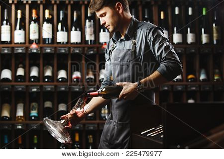 Bartender In Apron Pours Red Wine In Decanter In Cellar With Wooden Shelves Full Of Vintage Bottles