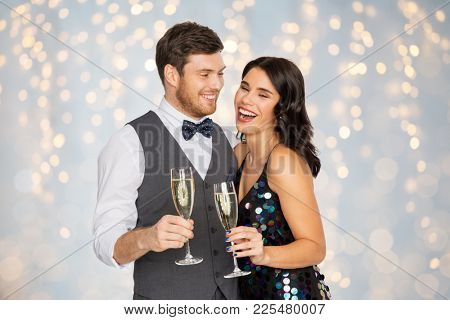 celebration and holidays concept - happy couple with glasses drinking non alcoholic champagne at party over festive lights background