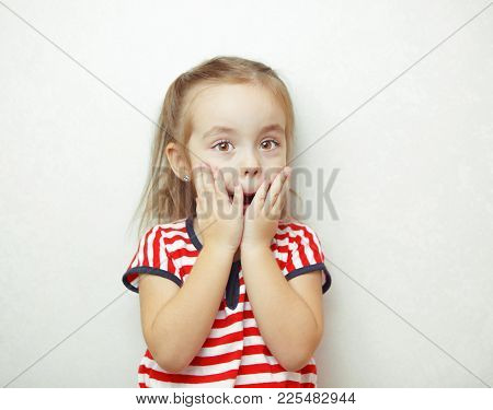 Child With Hazel Eyes, Expressing Surprise Emotion By Putting Hands On Face And Making Surprising So