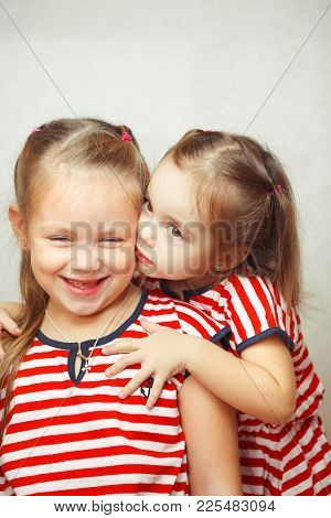 Children Hug Each Other And Smile, Happy Kids Wearing Dresses Of The Same Type, Tall Girl Looking Sm