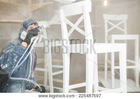 Man Painting Chair Into White Paint In Respiratory Mask. Application Of Flame Retardant Ensuring Fir