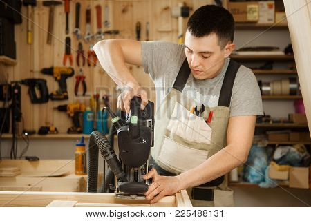 Man Working With Carving Equipment In Workshop. Electronic Device Makes Chinseling Groove In Wooden