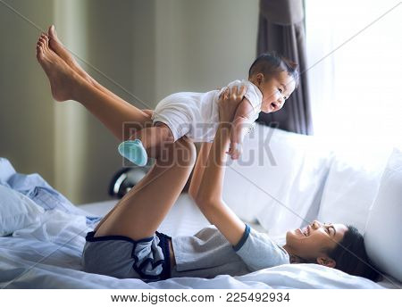 Asian Mother And Baby Play Togather In Bed Room In A House With Fly Action.