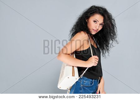 Sexy Young Girl With Black Curly Hair Carrying White Backpack With A Pattern And A Zipper. She Wears