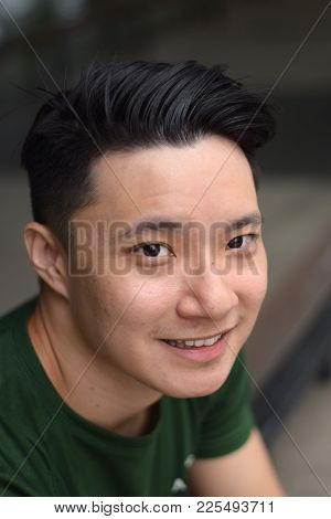 A Young Asian Male Chinese Looking At Camera Smiling