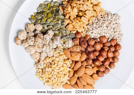 Many Different Nuts On A White Plate Are Shot Close-up From Above