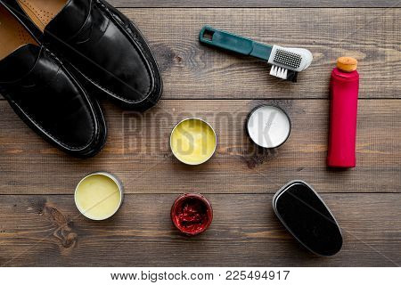 Shoe Care Products. Leather Men Shoes, Shoe Polish, Brushes, Wax On Dark Wooden Background Top View.