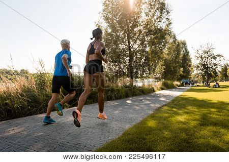 Young Multi Ethnic Joggers Running Together In Park