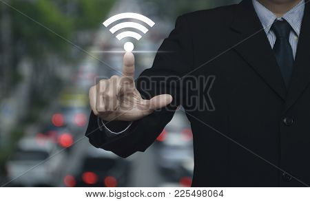 Businessman Pointing To Wi-fi Button Over Blur Of Rush Hour With Cars And Road, Technology And Inter