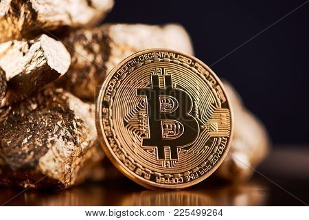 Golden Bitcoin Next To Gold Lumps Representing Futuristic World Trends Both Isolated On Black Backgr