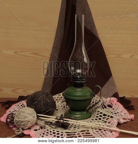 Kerosene Iron Lamp With Handle Tangle Of Threads With Knitting Needles On A Dark Background