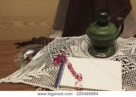 Kerosene Iron Lamp With A Pen And A Notebook On A Dark Background
