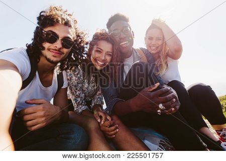 Group Of Friends Sitting Together On Mountain Top And Taking Self Portrait With Mobile Phone. Young